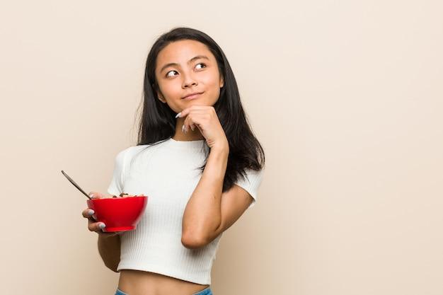 Jonge aziatische vrouw die een graangewassenkom houdt die zijwaarts met twijfelachtige en sceptische uitdrukking kijkt.