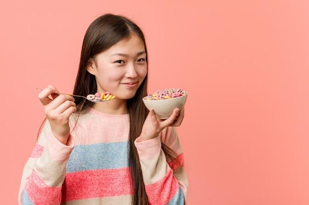 Jonge aziatische vrouw die een graangewassenkom houdt