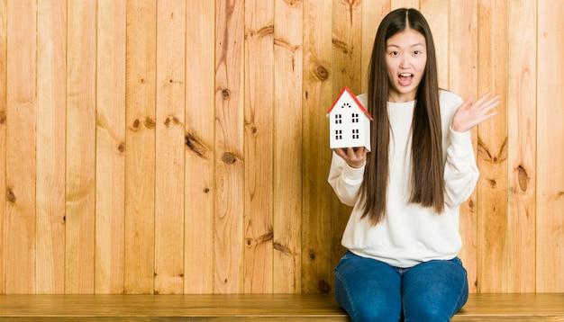 Jonge aziatische vrouw die een huispictogram houdt dat een overwinning of een succes viert