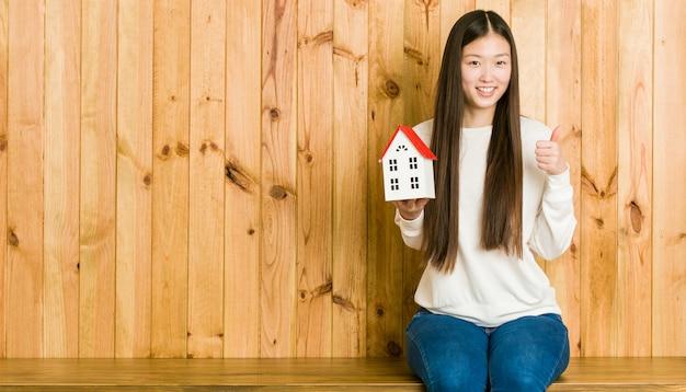 Jonge aziatische vrouw die een huispictogram houdt dat en duim tegenhoudt opheft