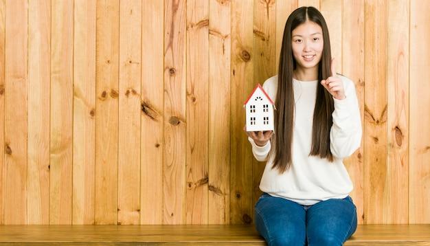 Jonge aziatische vrouw die een huispictogram houdt dat nummer één met vinger toont.