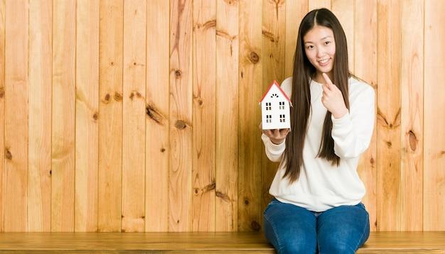 Jonge aziatische vrouw die een huispictogram houdt richtend met vinger op u alsof uitnodigend dichterbij kom.