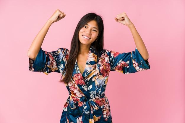 Jonge aziatische vrouw die een kimonopyjama draagt die sterktegebaar met wapens, symbool van vrouwelijke macht toont
