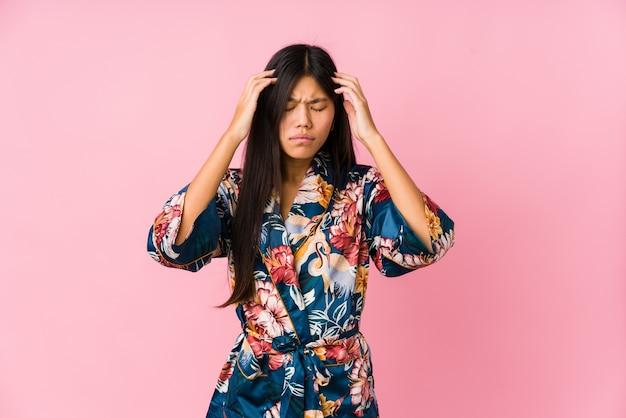Jonge aziatische vrouw die een kimonopyjama draagt die tempels aanraakt en hoofdpijn heeft.