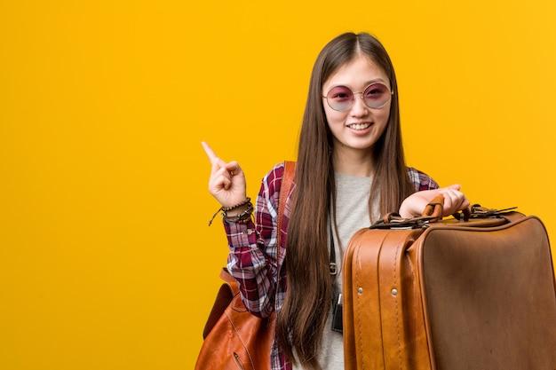Jonge aziatische vrouw die een koffer houden glimlachend vrolijk wijzend met weg wijsvinger.