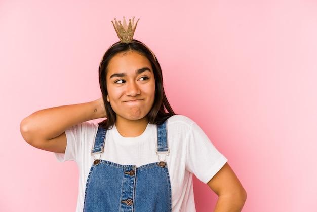 Jonge aziatische vrouw die een kroon draagt die geïsoleerd wordt wat betreft achterkant van het hoofd, denkt en een keuze maakt.