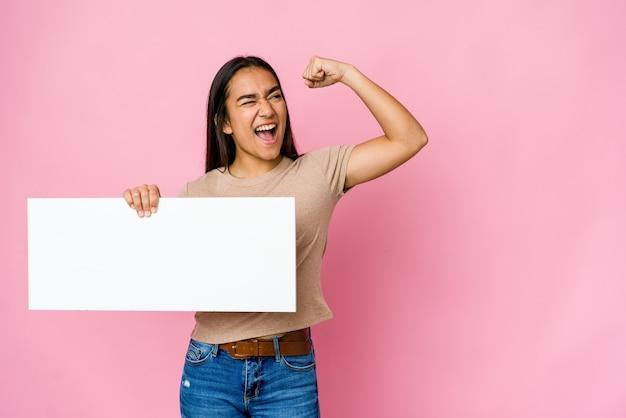 Jonge aziatische vrouw die een leeg document voor wit houdt iets over geïsoleerde muur die vuist opheft na een overwinning, winnaarconcept