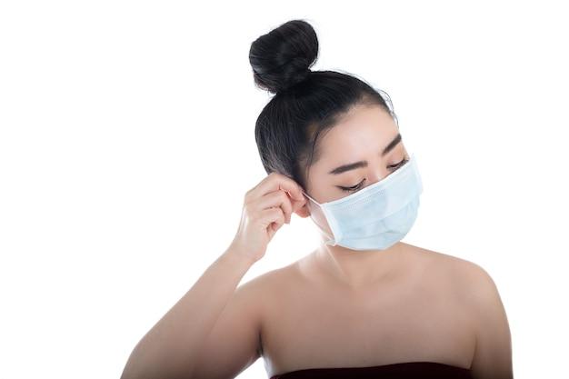 Jonge aziatische vrouw die een medisch masker opzet