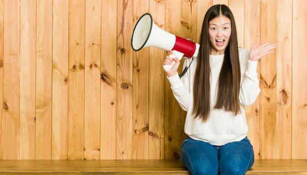 Jonge aziatische vrouw die een megafoon houdt die een overwinning of een succes viert