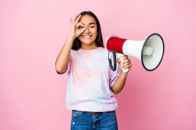 Jonge aziatische vrouw die een megafoon houdt die op roze opgewekte muur wordt geïsoleerd die ok gebaar op oog houdt.