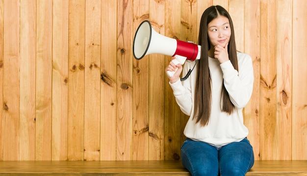 Jonge aziatische vrouw die een megafoon houdt die zijdelings met twijfelachtige en sceptische uitdrukking kijkt.