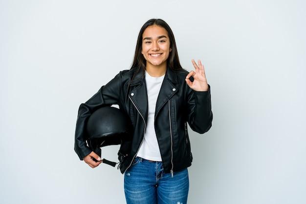 Jonge aziatische vrouw die een motorhelm over geïsoleerde muur houdt vrolijk en zeker tonend ok gebaar.
