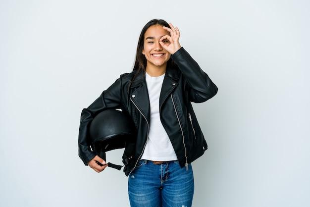 Jonge aziatische vrouw die een motorhelm over geïsoleerde opgewekte muur houdt die ok gebaar op oog houdt.