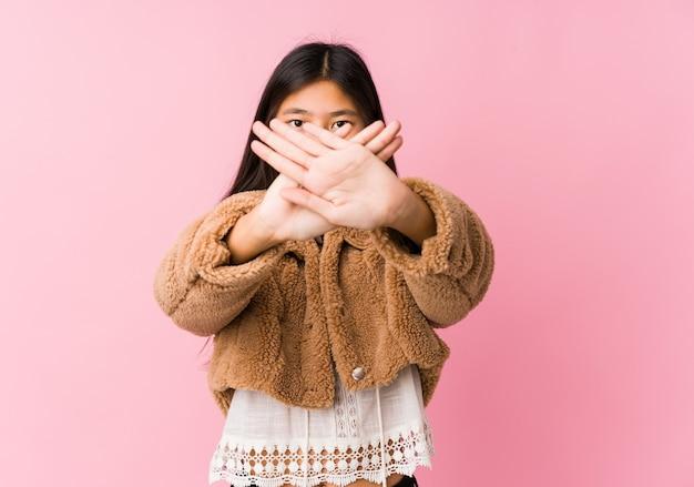 Jonge aziatische vrouw die een ontkenningsgebaar doet
