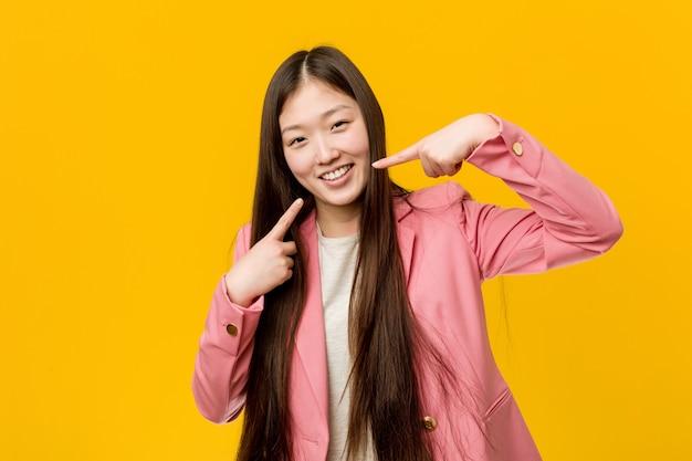 Jonge aziatische vrouw die een pak draagt