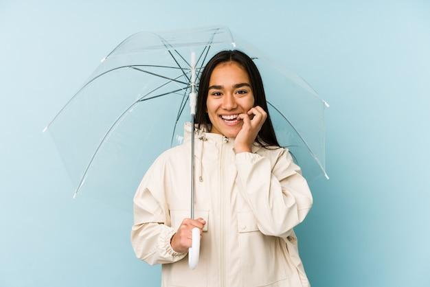Jonge aziatische vrouw die een paraplu houdt die vingernagels bijt