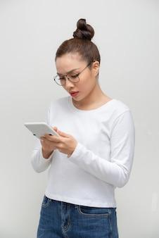 Jonge aziatische vrouw die een rekenmachine toont.