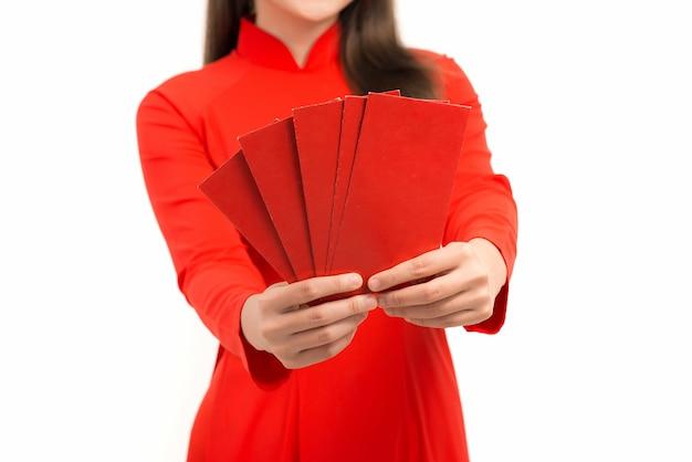 Jonge aziatische vrouw die een rode envelop toont voor het nieuwe maanjaar terwijl ze ao dai over wit draagt.