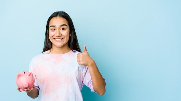 Jonge aziatische vrouw die een roze bank over geïsoleerde muur houdt die en duim opheft