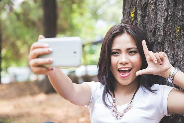 Jonge aziatische vrouw die een selfie nemen terwijl openlucht zitten