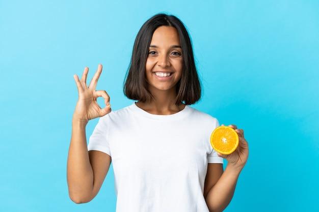 Jonge aziatische vrouw die een sinaasappel houdt die op blauw wordt geïsoleerd dat ok teken met vingers toont