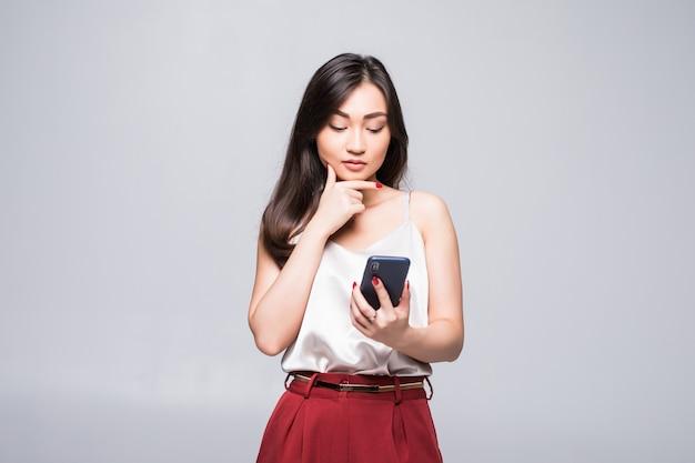 Jonge aziatische vrouw die een slimme telefoon met behulp van die op witte muur wordt geïsoleerd.