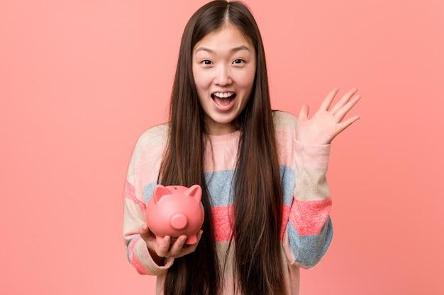 Jonge aziatische vrouw die een spaarvarken houdt dat een overwinning of een succes viert