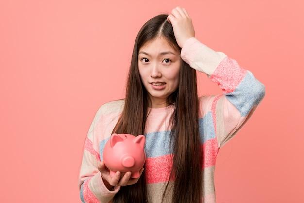 Jonge aziatische vrouw die een spaarvarken houdt dat wordt geschokt, heeft zij belangrijke vergadering herinnerd.