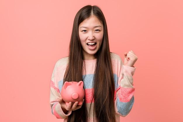 Jonge aziatische vrouw die een spaarvarken houdt dat zorgeloos en opgewekt juicht. overwinning concept.