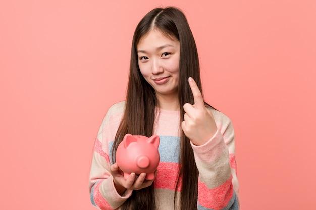 Jonge aziatische vrouw die een spaarvarken houdt richtend met vinger op u alsof uitnodigend dichterbij kom.