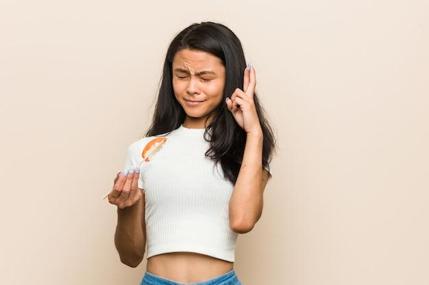 Jonge aziatische vrouw die een sushistuk houden die vingers kruisen voor het hebben van geluk