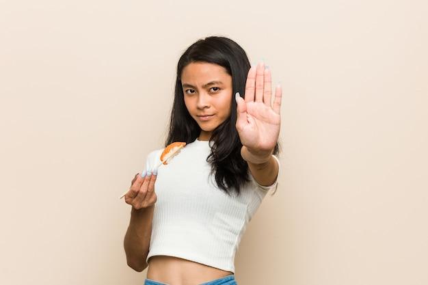 Jonge aziatische vrouw die een sushistuk houdt dat zich met uitgestrekte hand bevindt die eindeteken toont, dat u verhindert.