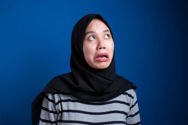 Jonge aziatische vrouw die een traditionele islamitische hijab-sjaal draagt, die er moe en verveeld uitziet met depressieproblemen tegen een blauwe achtergrond