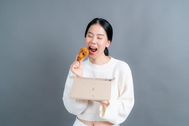 Jonge aziatische vrouw die een trui met een blij gezicht draagt en geniet van het eten van gebakken kip