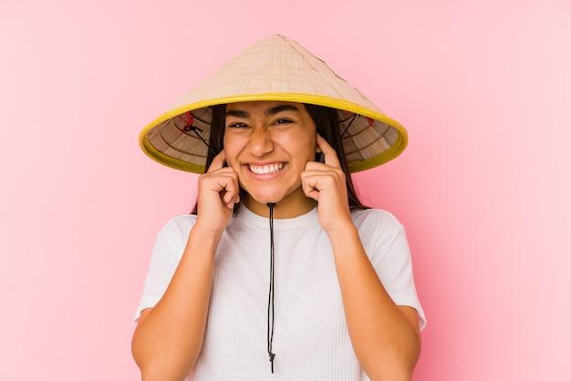 Jonge aziatische vrouw die een vietnamese geïsoleerde hoed draagt jonge aziatische vrouw die een vietnam hatcovering oren met handen draagt.