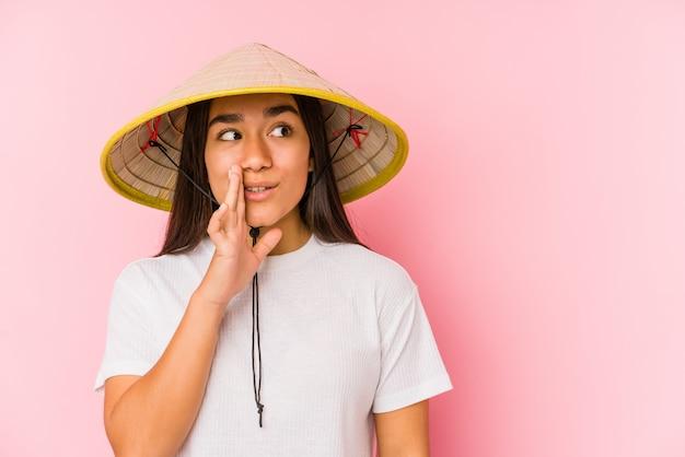 Jonge aziatische vrouw die een vietnamese hoed draagt die een geheim zegt