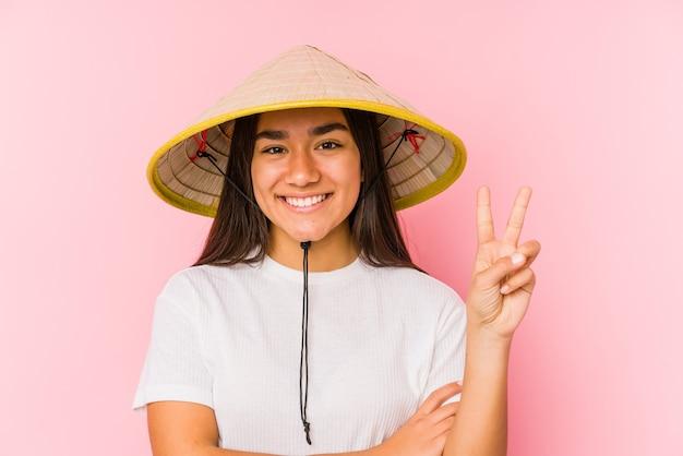 Jonge aziatische vrouw die een vietnamese hoed draagt, geïsoleerd jonge aziatische vrouw die een vietnamese hatshowing nummer twee met vingers draagt.