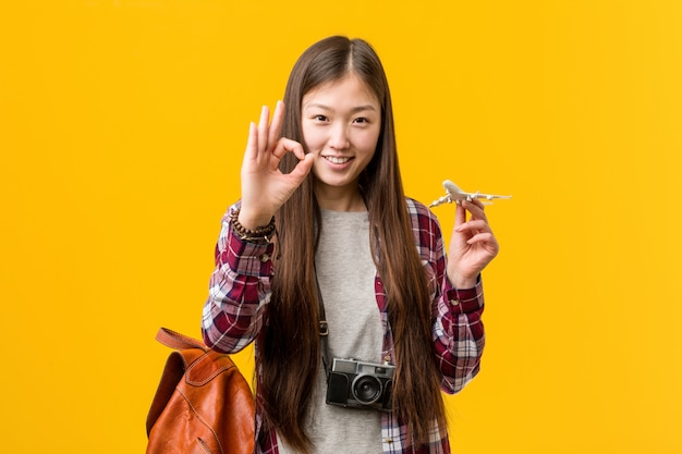 Jonge aziatische vrouw die een vliegtuigpictogram vrolijk en zeker houdt die ok gebaar toont.