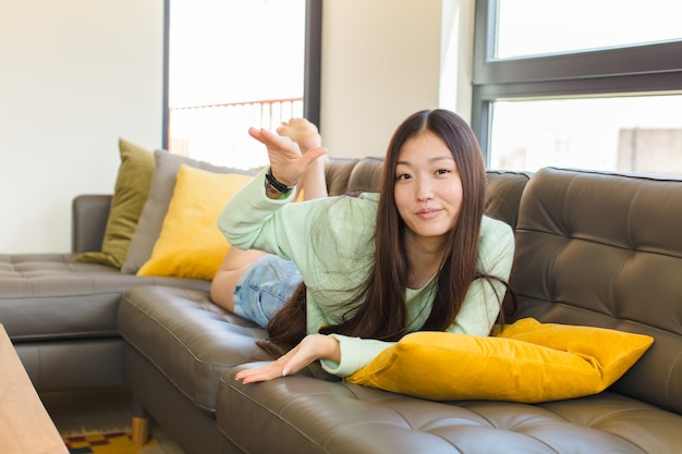 Jonge aziatische vrouw die een voorwerp met beide handen op zijexemplaarruimte houdt, een voorwerp toont, aanbiedt of adverteren