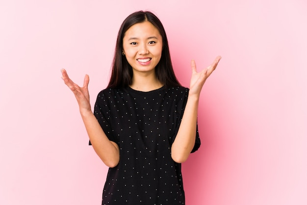 Jonge aziatische vrouw die elegante geïsoleerde kleren draagt ontvangend een prettige verrassing, opgewekte en opheffende handen.