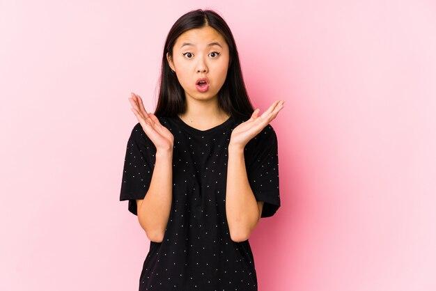 Jonge aziatische vrouw die elegante geïsoleerde kleren verrast en geschokt draagt.