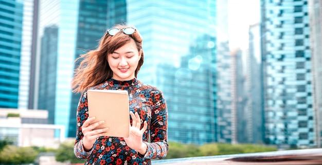 Jonge aziatische vrouw die elektronisch apparaat in moderne stad met behulp van