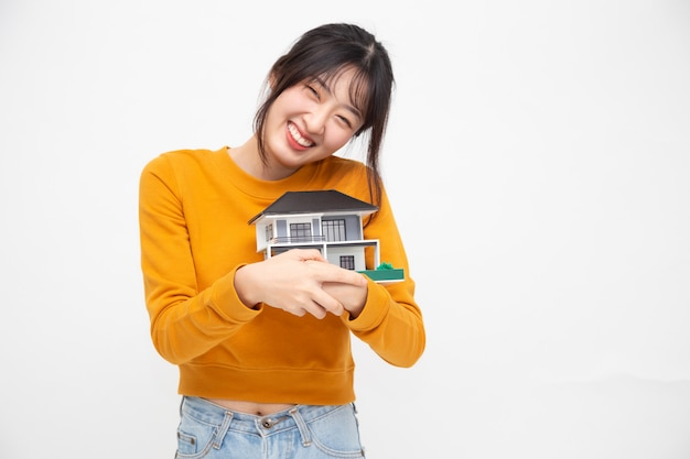 Jonge aziatische vrouw die en de steekproefmodel van het droomhuis over wit glimlachen koesteren