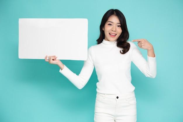 Jonge aziatische vrouw die en leeg wit aanplakbord toont dat op groene achtergrond wordt geïsoleerd