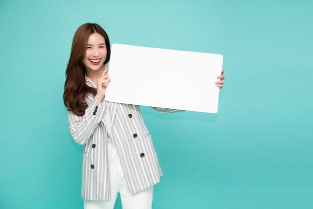 Jonge aziatische vrouw die en leeg wit aanplakbord toont houdt.