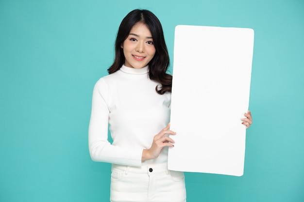 Jonge aziatische vrouw die en leeg wit bord toont dat op groene muur wordt geïsoleerd