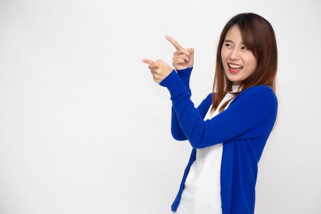 Jonge aziatische vrouw die en naar lege exemplaarruimte glimlacht richt die op witte muur wordt geïsoleerd