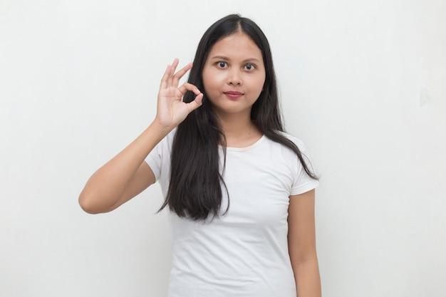 Jonge aziatische vrouw die en ok teken met handgebaar glimlacht maakt