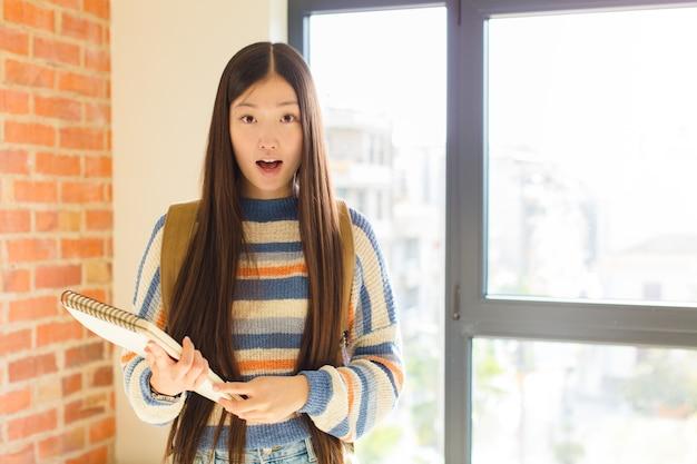 Jonge aziatische vrouw die erg geschokt of verrast kijkt, met open mond staart en wauw zegt