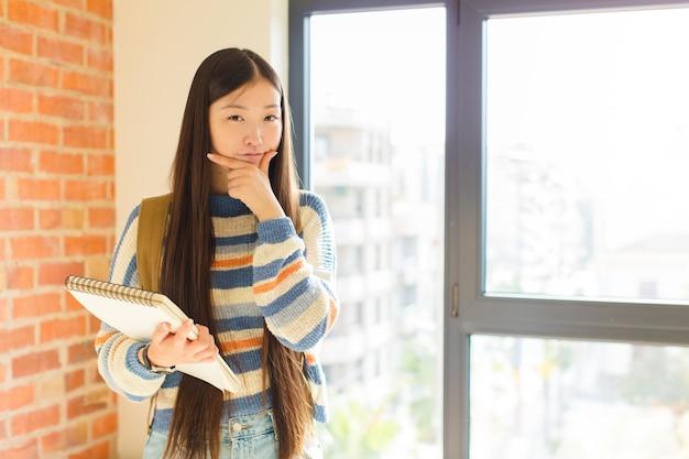 Jonge aziatische vrouw die ernstig, bedachtzaam en wantrouwend kijkt, met één gekruiste arm en hand op kin, wegingsopties